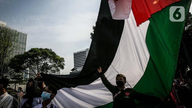 Massa yang tergabung dalam Aliansi Pemuda Indonesia untuk Palestina mengibarkan bendera Palestina saat aksi solidaritas di depan Kedutaan Besar Amerika Serikat, Jakarta, Selasa (18/5/2021). Massa mengajak masyarakat Indonesia untuk terus mendukung dan membantu Palestina. (Liputan6.com/Faizal Fanani)