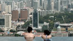 Wisatawan melihat pemandangan kota yang memukau dari kolam renang atap hotel Marina Bay Sands. Singapura dinobatkan sebagai kota paling mahal di dunia untuk tiga tahun berturut-turut di atas Zurich, Hong Kong, Jenewa dan Paris. (AFP PHOTO/Roslan RAHMAN)