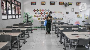 Petugas menyemprotkan disinfektan pada salah satu ruang kelas di SD Negeri Malaka Jaya 07 Pagi, Jakarta, Kamis (26/8/2021). Pemprov DKI berencana membuka kembali sekolah untuk pembelajaran tatap muka terbatas pada Senin (30/8) setelah status PPKM turun ke level 3. (merdeka.com/Iqbal S Nugroho)