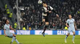 Penyerang Juventus, Cristiano Ronaldo menyundul bola dari kawalan pemain Atletico Madrid, Marcos Llorente pada pertandingan Grup D Liga Champions di stadion Allianz di Turin, Italia (26/11/2019). Juventus menang tipis atas Atletico Madrid 1-0. (AP Photo/Antonio Calanni)