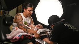 Seorang wanita membawa bayinya saat menato kakinya selama Expotattoo Colombia 2019 di Medellin, departemen Antioquia (2/6/2019). Para penggila tato antusias untuk mentato tubuhnya di festival tato terbesar di negara tersebut. (AFP Photo/Joaquim Sarmiento)