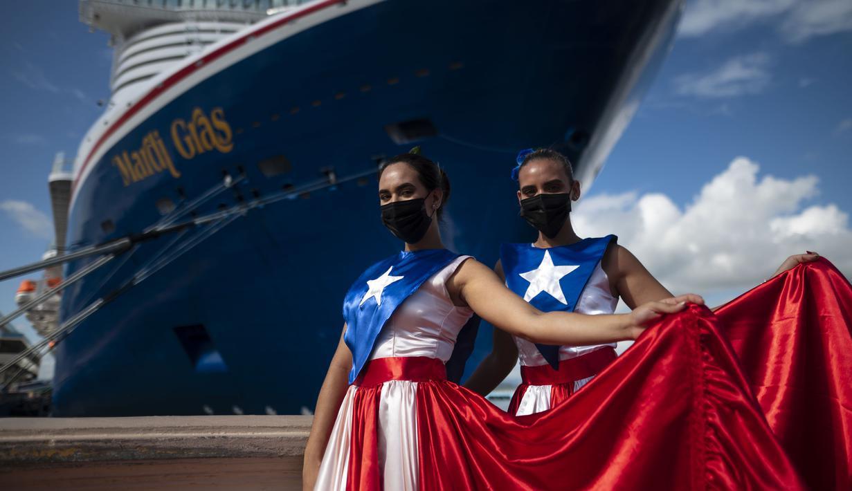 Ivanelis Jimenez (depan) dan Veronica Barreto mengenakan gaun bendera Puerto Rico saat menyambut penumpang kapal pesiar Mardi Gras Carnival yang berlabuh di Teluk San Juan, Puerto Rico, Selasa (3/8/2021). (AP Photo/Carlos Giusti)
