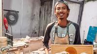 Potret Bayu Putro bersama salah satu produk hiasan dinding yang terbuat dari resin dan kayu. (Sumber: dokumentasi Pluei)