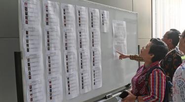 Sejumlah Capim KPK melihat daftar nama di Pusdiklat Kemensetneg, Jakarta, Minggu (28/7/2019). Tes psikologi ini diikuti oleh 104 peserta setelah melalui proses seleksi pada tes administrasi. (Liputan6.com/Herman Zakharia)