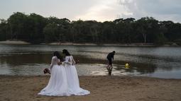 Jaiane Pereira Marsal dan Gislaine Pereira de Araujo bersiap difoto untuk album pernikahan dengan latar belakang hutan hujan Amazon di pantai sungai Jamanxim, Brasil (2/9/2019). Jaiane dan Gislaine akan menikah hari Senin ini dan ibunya merayakan ultah pernikahan ke-25. (AP Photo/Leo Correa)