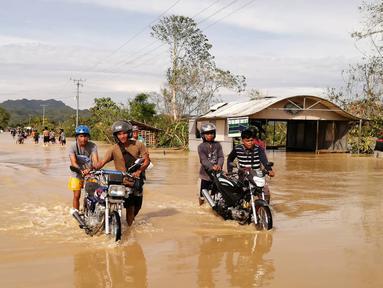 Pengendara sepeda motor melintasi jalan raya yang banjir usai terjangan topan Phanfone di Ormoc City, Provinsi Leyte, Filipina, Rabu (25/12/2019). Topan membuat jutaan warga di negara yang mayoritas beragama Katolik itu merayakan Natal dengan kesedihan. (RONALD FRANK DEJON/AFP)