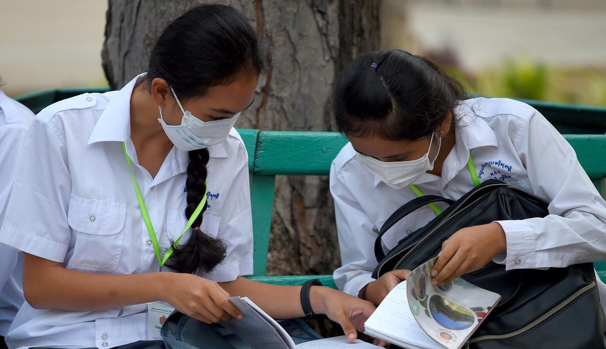 Dua siswi mengenakan masker membaca buku di sebuah sekolah di Phnom Penh (28/1/2020). Kementerian kesehatan Kamboja melaporkan kasus pertama virus korona mematikan di negara itu pada 27 Januari. (TANG CHHIN SOTHY/AFP)