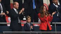 (Kiri ke Kanan) Pangeran William, Duke of Cambridge, Pangeran George dari Cambridge, dan Catherine, Duchess of Cambridge, merayakan gol Inggris ke gawang Jerman pada pertandingan babak 16 besar Euro 2020 di Stadion Wembley, London, Inggris, Selasa (29/6/2021). (Photo by JUSTIN TALLIS/POOL/AFP)