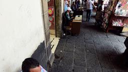 Seorang notaris serius menulis dokumen di Santo Domingo Square, Meksiko, (23/8). Notaris yang berada di pinggir jalan ini menerima jasa menulis surat terkait hukum perdata, lamaran kerja, wasiat, bahkan surat cinta. (AFP PHOTO/ALFREDO ESTRELLA)