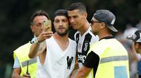Seorang suporter Juventus berselfie dengan Cristiano Ronaldo selama pertandingan persahabatan antara Juventus A dan tim B, di Villar Perosa, Italia utara, (12/8). Suporter tersebut masuk ke lapangan pada babak pertama. (AP Photo/Antonio Calanni)