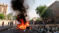 Pengunjuk rasa antipemerintah membakar sejumlah benda dan memblokir jalan saat menggelar protes di Baghdad, Irak, Rabu (2/10/2019). Ribuan demonstran berhadapan dengan tembakan dan gas air mata dalam unjuk rasa yang terjadi di sejumlah kota di Irak. (AP Photo/Hadi Mizban)