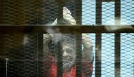 Mantan Presiden Mesir Mohammed Morsi mengenakan seragam merah saat menjalani sidang di Kairo, Mesir, 18 Juni 2016. Mohammed Morsi sesaat setelah dia berbicara dari balik sangkar kaca, tempat di mana dia ditahan selama sesi persidangan. (MOHAMED EL-SHAHED/AFP)