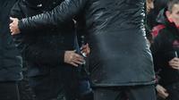 Manajer Manchester United, Jose Mourinho berjabat tangan dengan manajer Liverpool, Jurgen Klopp seusai pertandingan  lanjutan pekan ke-17 Premier League di Stadion Anfield, Minggu (16/12). MU tumbang di markas Liverpool dengan skor 1-3. (Paul ELLIS / AFP)