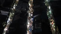 Orang-orang berjalan melalui gang-gang sempit yang dikelilingi bar dan restoran kecil di Golden Gai di distrik Shinjuku Tokyo (28/7/2019). Kawasan Ini terdiri dari enam jalanan sempit yang menghubungkan lorong yang lebih sempit yang hanya cukup dilewati satu orang. (AP Photo/Jae C.Hong)