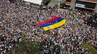 Puluhan ribu demonstran antipemerintah menuntut pengunduran diri Presiden Venezuela Nicolas Maduro di Caracas, Venezuela, Sabtu (2/2). Tokoh oposisi Juan Guaido mendeklarasikan dirinya sebagai 'presiden interim'. (AP Photo/Juan Carlos Hernandez)