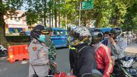 Aparat gabungan memeriksa pengendara roda dua saat penerapan PSBB corona di Kota Bogor. (Achmad Sudarno/Liputan6.com)