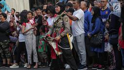 Anggota polisi wanita (polwan) melakukan atraksi saat pertunjukan Tari Reog Ponorogo di area car free day kawasan Bundaran Hotel Indonesia (HI), Jakarta, Minggu (28/4/2019). Kegiatan untuk memperingati Hari Kartini tersebut turut diramaikan oleh sejumlah polwan. (Liputan6.com/Faizal Fanani)