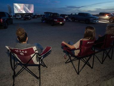 """Orang-orang menonton film """"Encore Drive-In Nights Presents Blake Shelton,"""" di Stars & Stripes Drive-In Theatre, Texas pada 25 Juli 2020. Konser yang menampilkan Blake Shelton bersama Gwen Stefani ini ditayangkan di bioskop drive-in seluruh Amerika Utara. (Mikala Compton/Herald-Zeitung via AP)"""