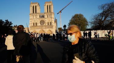 Seorang perempuan melintasi orang-orang yang berhenti di depan Katedral Notre Dame saat kembali membunyikan lonceng utamanya di Paris, Rabu (15/4/2020). Lonceng utama katedral kembali dibunyikan setelah satu tahun mengalami kebakaran yang sampai mengejutkan seluruh warga dunia. (AP/Christophe Ena)