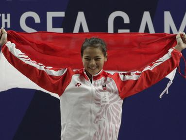 Lifter Aisyah Windy mengibarkan bendera saat naik podium usai mendapatkan medali emas SEA Games 2019 cabang angkat besi nomor 49 kg di Stadion Rizal Memorial, Manila, Minggu (1/12). Dirinya meraih emas dengan total angkatan 104 kg. (Bola.com/M Iqbal Ichsa