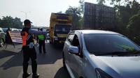 Petugas gabungan sedang memeriksa pengendara yang hendak masuk ke Kota Bogor di check point keluar Tol Jagorawi, Rabu (15/4/2020). Pemeriksaan ini merupakan penerapan PSBB dalam menekan penyebaran Covid-19. (Liputan6.com/Achmad Sudarno)