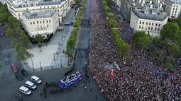Jutaan fans menyambut kedatangan timnas Prancis di Champs-Elysee avenue, Paris, (16/7/2018). Sambutan meriah tersebut adalah bagian dari perayaan keberhasilan Prancis meraih trofi Piala Dunia 2018. (AFP/Bertrand Guay)