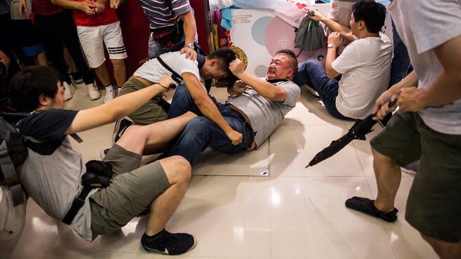 Demonstran pro-China (kanan) berkelahi dengan demonstran antipemerintah di sebuah pusat perbelanjaan di Distrik Kowloon Bay, Hong Kong, Sabtu (14/9/2019). Bentrokan yang awalnya hanya adu mulut berubah menjadi saling baku pukul. (ISAAC LAWRENCE/AFP)