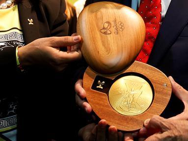 Komite dan Presiden Olimpiade Internasional (IOC) menunjukkan medali emas saat peluncuran medali Olimpiade 2016 Rio de Janeiro, Brasil (14/6). (REUTERS/ Sergio Moraes)