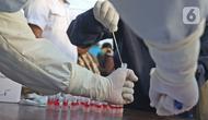 Petugas medis mengambil sampel penumpang KRL Commuter Line saat tes swab dengan metode polymerase chain reaction (PCR) di Stasiun Bekasi, Selasa, (5/5/2020). Pemkot Bekasi melakukan tes swab secara massal setelah tiga penumpang KRL dari Bogor terdeteksi virus corona. (Liputan6.com/Herman Zakharia)