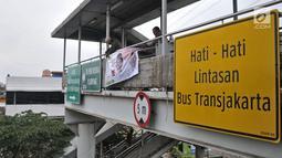 Petugas Satpol PP mencopot spanduk APK yang terpasang di JPO di sepanjang Jalan Yos Sudarso, Jakarta, Rabu (13/3). Bawaslu menginstruksikan Pemkot se-DKI Jakarta untuk menertibkan APK yang dipasang di sembarang tempat. (merdeka.com/Iqbal S. Nugroho)