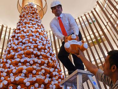 Seorang staff menyusun pohon Natal yang terbuat dari boneka beruang teddy di lobi sebuah hotel di Bangalore, India, Rabu (28/11). Ratusan boneka beruang disusun sedemikian rupa hingga membentuk pohon natal cantik. (MANJUNATH KIRAN / AFP)