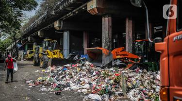 Petugas PPSU menggunakan kendaraan alat berat untuk mengangkut tumpukan sampah di kolong tol Wiyoto Wiyono, Tanjung Priok, Jakarta, Selasa (5/11/2019). Kolong Tol Tol Wiyoto-Wiyono berubah menjadi tempat penampungan sampah rumah tangga dari tiga kelurahan di kawasan itu. (Liputan6.com/Faizal Fanani)