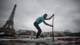 Peserta Nautic Paddle Race atau lomba dayung sambil berdiri melintas dekat Menara Eiffel di Sungai Seine, Paris, Minggu (8/12/2019). Sekitar 1000 pesaing ikut serta dalam lomba sejauh 11 kilometer menyeberangi sungai Seine dengan pemandangan kota Paris. (Photo by Olivier MORIN / AFP)