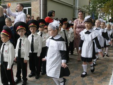 Orang tua mengambil foto ketika taruna muda menghadiri upacara pada hari pertama sekolah di salah satu sekolah Kadet terbaik, lyceum, di Kiev, Senin (3/9). Ukraina menandai Hari Pengetahuan, sebagai dimulainya tahun ajaran baru. (AP Photo/Efrem Lukatsky)