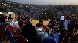 Sekelompok anak yatim dari kota utara Irbid berbuka puasa setelah menyaksikan penembakan meriam sebagai tanda berbuka puasa di Benteng Amman, 13 Mei 2019. Saat tiba waktu Maghrib yang sekaligus menjadi penanda waktu berbuka puasa di Yordania, ditandai dengan tembakan meriam. (REUTERS/Muhammad Hamed)