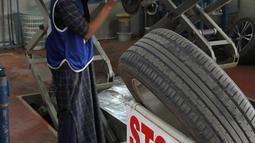 Montir perempuan Pakistan Uzma Nawaz (24) memperbaiki mobil di sebuah bengkel kota Multan, 1 September 2018. Uzma berusaha keras mendapat pekerjaan di bengkel karena kebanyakan pemiliknya memandang sebelah mata perempuan teknisi. (S.S. Mirza/AFP)
