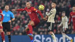 Bek Liverpool, Virgil van Dijk, berebut bola dengan gelandang Manchester United, Andreas Pereira, pada laga Premier League di Stadion Anfield, Liverpool, Minggu (19/1). Liverpool menang 2-0 atas MU. (AFP/Paul Ellis)