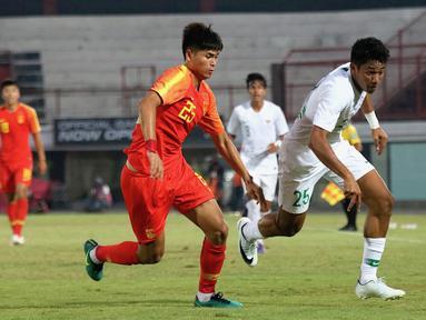 Striker China U-19, Tayier Xiaokaitijiang, berebut bola dengan striker Timnas Indonesia U-19, Serdy Ephy Fano Boky, pada laga ujicoba di Stadion I Wayab Dipta, Bali, Minggu (20/10). Indonesia kalah 1-3 dari China. (Bola.com/Aditya Wany)