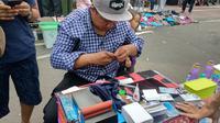 Aksi Sugeng memperbaiki kartu yang rusak di CFD Bundaran HI, Jakarta Pusat, Minggu (31/3/2019). (Liputan6.com/Ika Defianti)