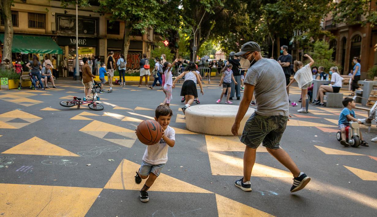 """Seorang anak bermain dengan ayahnya di pusat kota Barcelona, Spanyol (25/6/2020). Spanyol telah memasuki tatanan """"Normal Baru"""" pada 21 Juni, dengan mengizinkan kembali warga untuk bebas bepergian di seluruh wilayah negara tersebut. (Xinhua/Balai Kota Barcelona)"""