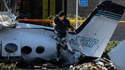 Petugas investigasi mengamati reruntuhan pesawat kecil yang jatuh ke area parkir pusat perbelanjaan South Coast Plaza di Santa Ana, California, Senin (6/8). Pesawat Cessna bermesin ganda itu jatuh saat akan menuju Bandara John Wayne. (AP/Jae C. Hong)