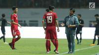 Pelatih Timnas Indonesia U-19, Indra Sjafri (kanan) memberi arahan pada Hanis Saghara Putra saat laga persahabatan melawan Thailand U-19 di Stadion Wibawa Mukti, Cikarang, Jawa Barat, Minggu (8/10). Indonesia menang 3-0. (Liputan6.com/Helmi Fithriansyah)