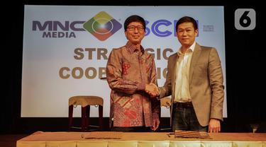 CEO PT Surya Citra Media Tbk Sutanto Hartono (kiri) bersalaman dengan Direktur Utama PT Media Nusantara Citra Tbk David Fernando Audy usai menandatangani MoU kerja sama di Jakarta, Kamis (12/12/2019). SCM dan MNC menjalin kerja sama untuk meningkatkan sektor bisnis. (Liputan6.com/Faizal Fanani)