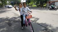 Dua orang pria tampak berboncengan menaiki sepeda ontel warna pink dengan plat bertuliskan 'NKRI' menggunakan topeng Jokowi dan Prabowo. (Liputan6.com/Reza Efendi)