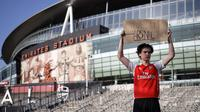Seorang penggemar Arsenal berdiri dengan memegang spanduk anti Liga Super Eropa di luar Stadion Emirates, London, Senin (19/4/2021). (Foto: AFP/Tolga Akmen)