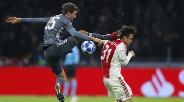 Gelandang Bayern Munchen, Thomas Mueller, menendang kepala bek Ajax Amsterdam, Nicolas Tagliafico, pada laga Liga Champions di Johan Cruyff Arena, Amsterdam, Rabu (12/12). Kedua tim bermain imbang 3-3. (AP/Peter Dejong)