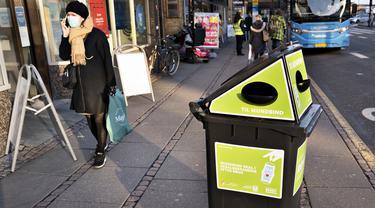Seorang pejalan kaki berjalan melewati tempat sampah untuk masker sekali pakai, di Aarhus Center, Denmark, Senin (23/11/2020). Kota Aarhus menempatkan seratus tempat sampah khusu berukuran 240 liter yang dapat menampung sekitar 3000 masker bekas. (Henning Bagger/Ritzau Scanpix/AFP)