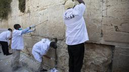 Para pekerja memindahkan catatan doa yang ditinggalkan pezirah dari sela-sela batu Tembok Ratapan, situs paling suci tempat orang Yahudi berdoa, di Yerusalem, Rabu (16/9/2020). Pandemi virus corona COVID-19 membayangi perayaan Tahun Baru Yahudi yang biasanya meriah. (AP Photo/Sebastian Scheiner)