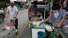 Seorang pria yang mengenakan masker membeli makanan dari warung kaki lima di kota Quezon, Filipina, Selasa (22/9/2020). Presiden Filipina Rodrigo Duterte mengatakan telah memperpanjang status masa darurat virus corona (Covid-19) di negaranya hingga satu tahun ke depan. (AP Photo/Aaron Favila)