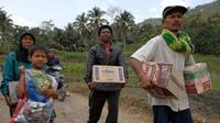 Warga membawa bantuan makanan yang diterimanya di Desa Cikangkareng, Cianjur. Gempa 7,3 SR mengakibatkan longsor tebing batu dan menewaskan 26 warga Desa Cikangkareng.(Antara)